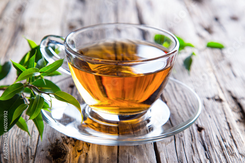 Foto op Canvas Thee Transparent cup of green tea on wooden background