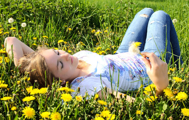 Young relaxed woman enjoys the spring between dandelions