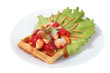 Brussels waffle on plate with lettuce leaf, paprika and fish.