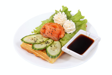 Belgian waffle with smoked salmon, lettuce leaf, cucumber slices