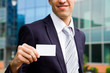 young businessman holding visit card in hand and standing in the