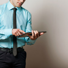 Serious young male executive using digital tablet against