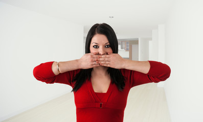 a young woman covers her mouth let alone in an empty room