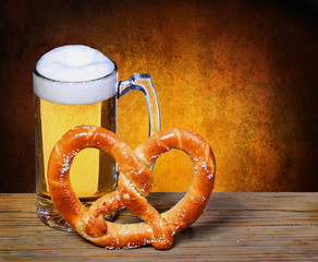 Beer Mug with German Pretzel on wooden table. isolated on white
