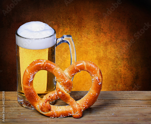 canvas print picture Beer Mug with German Pretzel on wooden table. isolated on white