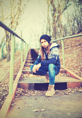 lonely girl teenager in hat sitting on stairs and sad autumn