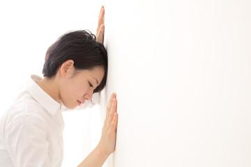壁に寄りかかる女性