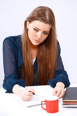 Pretty girl writing note thoughtfully