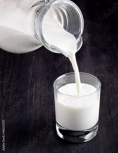 Milk pouring into a glass on black board