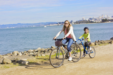 Mother and Daughter biking along the beach in San Francisco