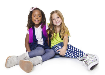 Two diverse little school children isolated on white