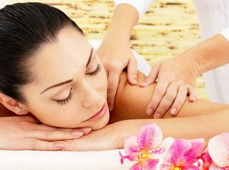 Woman having massage of shoulder in spa salon