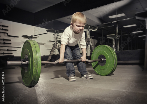 Leinwanddruck Bild Determined young boy trying to lift a heavy weight bar