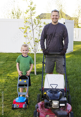 Father and Young Son mowing the lawn together