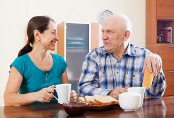 Smiling mature couple having tea