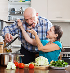 happy  mature couple cooking lunch