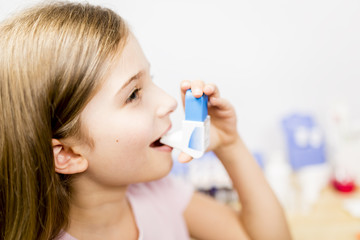 Allergy -  cute girl using  inhaler