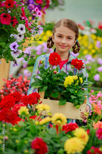 Planting - Lovely girl holding flowers in garden center