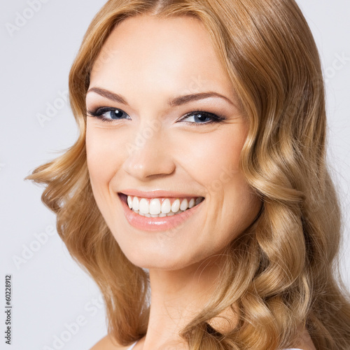 Young cheerful smiling woman, on gray