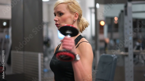 Fit strong young blond woman in a gym