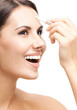 Smiling woman applying concealer on face, isolated