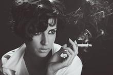 Élégante femme brune fumer une cigarette sur fond noir