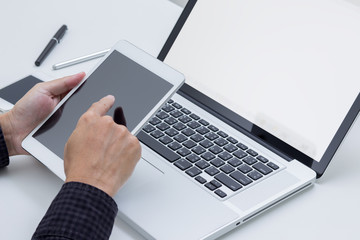Man hand working on tablet with blank screen laptop computer