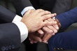 Businesspeople hands on top of each other as symbol of their uni