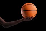 Fototapeta Basketball player holding a ball against dark background