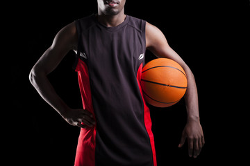 Image of a basketball player holding a ball against dark backgro