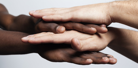 Multiracial hands together forming a pile over gray background