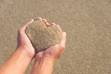 Hands holding a sand in form of heart