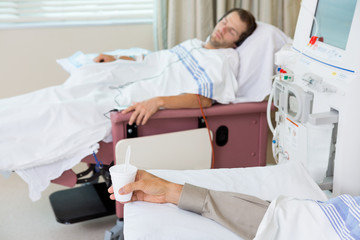 Patient Holding Glass Of Crushed Ice During Dialysis