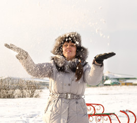 Happy woman throwing snow into the air