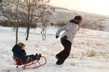 Mother running through the snow with a sled