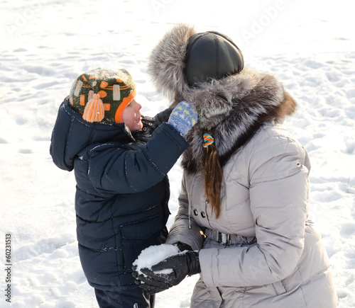 Cute boy playing with his mother in the snow