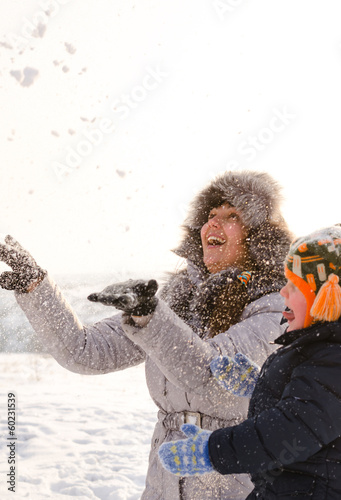 Laughing mother and son tossing snow in the air