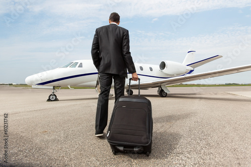 Fotobehang Luchthaven Businessman Walking Towards Corporate Jet