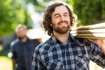 Carpenter Smiling While Carrying Planks With The Help Of Coworke