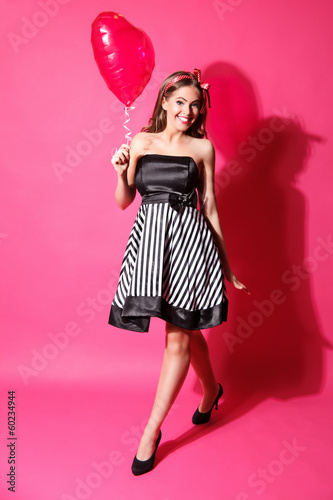 Portrait of a beautiful young woman walking with a heart shaped