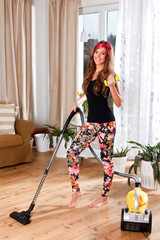 Beautiful young woman cleaning the living room while exercising