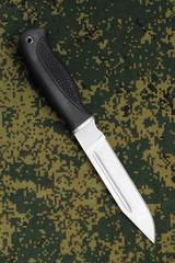 Military knife lying diagonally on camouflage background