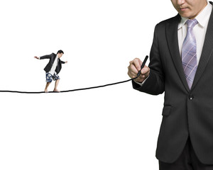 Businessman drawing line with another balancing on it