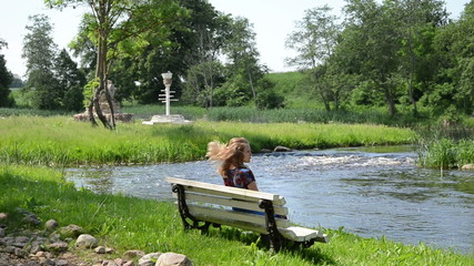 beautiful girl on  bench fast flowing stream admire nature