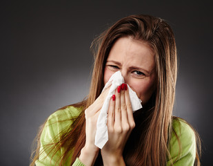 Caucasian female with flu blowing her nose