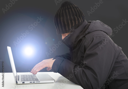 hacker working  with a laptop computer in the darkness