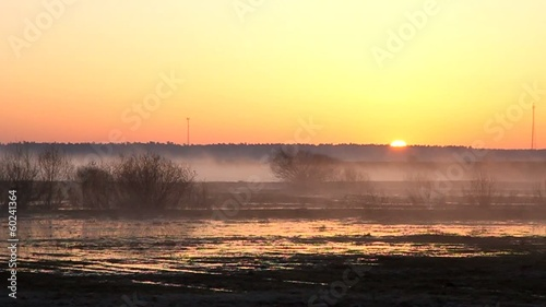 Sunrise, mist rises over the flooded field.