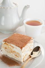 cake of tiramisu and tea with a teapot