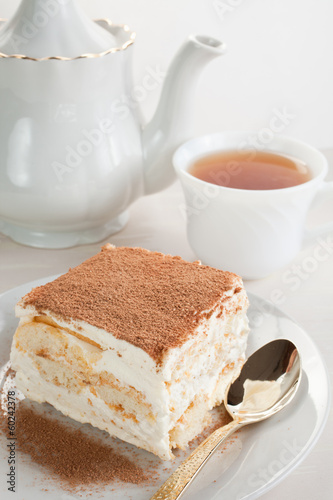 cake of tiramisu and tea with a teapot