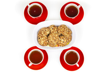 Four tea cups and plate of nut cookies